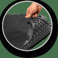 Une main soulève le tapis d'écurie afin de présenter le système de drainage en dessous du tapis